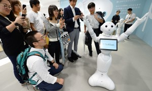 People look at humanoid robot 'Pepper'